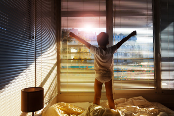 Boy standing on his bed and looking out the window