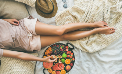 Summer healthy raw vegan clean eating breakfast in bed concept. Young girl wearing pastel colored home clothes taking fruit from tray full of fresh seasonal fruit. Top view, horizontal composition