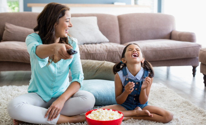 Mother and daughter watching television while having popcorn in living room at home
