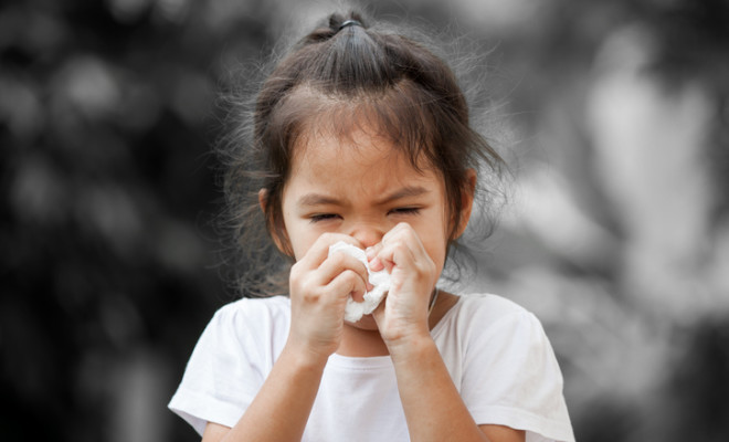 Sick little asian girl wiping or cleaning nose with tissue on her hand on black and white background