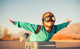 A young boy dressed in retro clothing and flying goggles dreams of flying on an exotic vacation at a far off destination. He is outstretching his arms like an airplane while on top of a suitcase and he has a happy expression on his face. Image taken in Utah, USA.