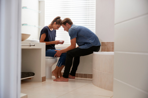 Couple Waiting For Result Of Home Pregnancy Test In Bathroom