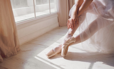 Pointe shoes on the feet of a ballerina in a white dance studio.