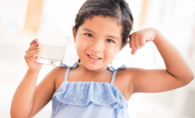 Beautiful Latin American girl drinking a glass of milk for growing strong