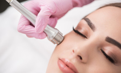 Close up of instrument in hand of doctor-cosmetologist, which is making procedure microdermabrasion of facial skin for beautiful young woman at beauty salon. Girl is lying with closed eyes