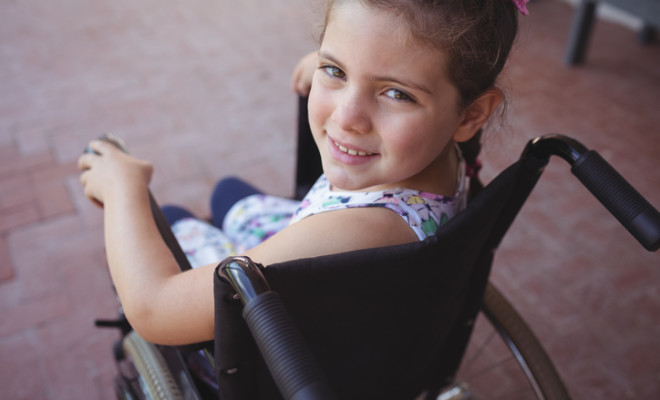High angle portrait of schoolgirl sitting on wheelchair at school