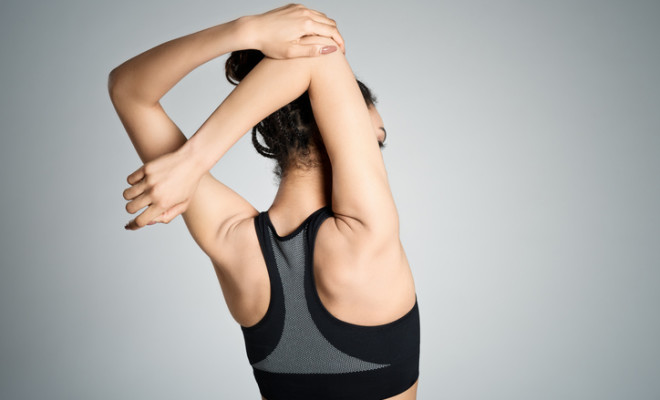 Back view of fit young woman restign after workout, stretching her arms. Studio shot, grey background.