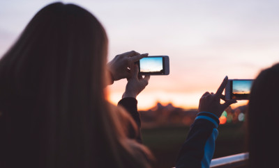 Two beautiful young girls in sports clothing standing on the bridge during the sunset, looking at the sky and holding their phones, photographing the sunset, feeling happy.