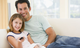 Man and young girl in living room with remote control smiling at camera lying on sofa