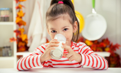 Beautiful Little Girl Drinking Glass of Milk