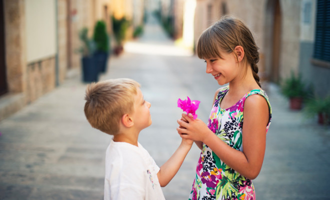 Little boy and girl looking in each other's eyes. The boy aged 4 is giving a flower to a girl aged 8. Mediterranean town street.