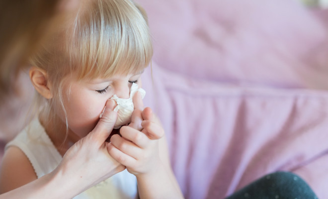 Child with runny nose. Mother helping to blow kid's nose with paper tissue. Seasonal sickness.