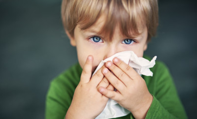 Cute sick boy aged 2 with runny nose tries to blow his nose.