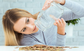 Beautiful woman with money jar. Bankruptcy concept.