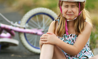 A little girl winces in pain after falling from her bike and skinning her knee