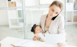 Busy female employee talking by smartphone and looking through important papers in office while baby daughter sleeping in her arms