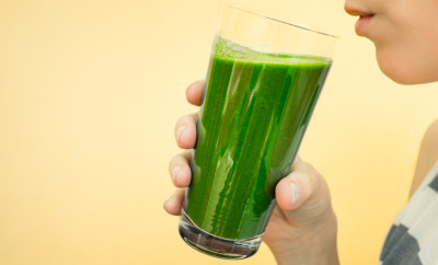 Closeup of female drinking green vegetable smoothie.