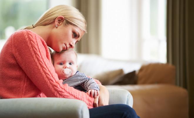 Mother Suffering From Post Natal Depression Hugging Child