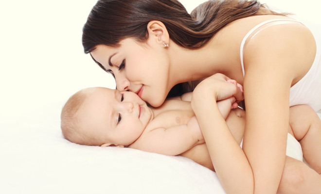 Portrait happy young loving mother kissing her baby