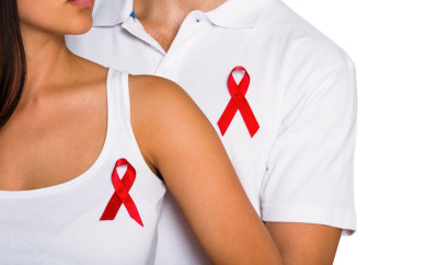 Couple supporting aids awareness together on white background