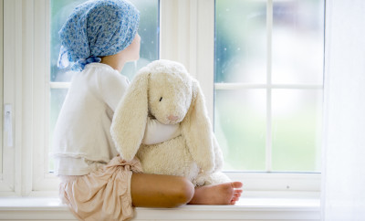 A little girl with cancer is sitting by the window and is looking outside. She is holding a stuffed animal.