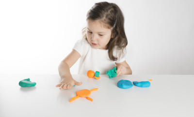 Toddler playing with play clay.