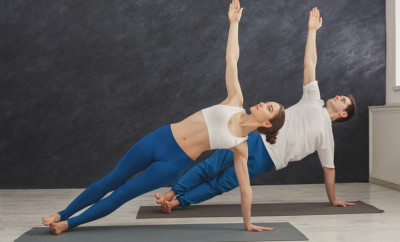 Fitness, man and woman training yoga in side plank pose at home. Young couple makes exercise, copy space