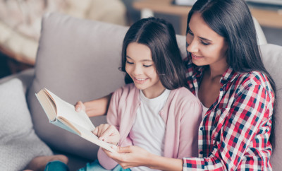 It's so interesting and exciting! Young smiling mother is reading a funny book for her cute sweet little daughter, they are doing homework and embracing and spending time together