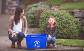 An ethnic mother and her young daughter are sitting by a recycling bin outside
