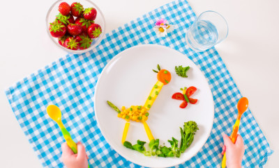 Healthy vegetarian lunch for little kids, vegetables and fruit served as animals, corn, broccoli, carrots and fresh strawberry helping children to learn eating right and clean, child's hands holding spoon