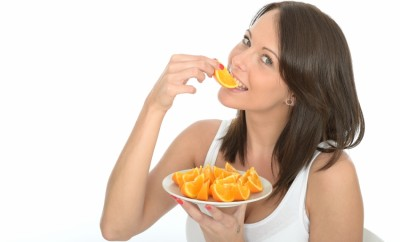Healthy Happy Young Woman Holding a Plate of Fresh Orange Segments