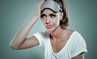 Conceptual portrait of tired blonde young woman wearing white t-shirt and sleeping mask on her forehead, suffering from headache. Standing against grey background with hand on her head. Studio shot.