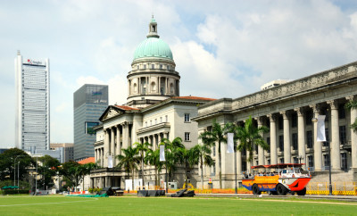 Singapore City, Singapore - March 19, 2011: City Hall, The image shows a view of the old City Hall building, constructed in the British coloniall style between 1926 and 1929. Singapore's Supreme court was also located here until 2005. The building overlokks the Padang and is now slated for redevelopment as the new National Art Gallery,  scheduled for completion in 2015.  Also, an unusual tourist vehicle belonging to Duck Tours can be seen transporting visitors around the city on a sightseeing tour.