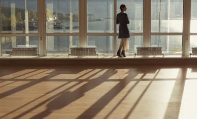 Woman standing near large window and looking to sunset. Big window, glass wall, warm room, sun and sea