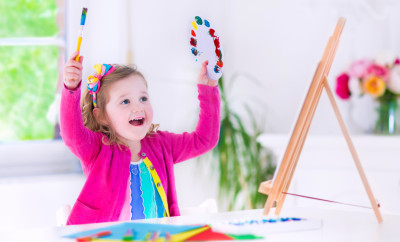 Cute happy little girl, adorable preschooler, painting with water color on canvas standing on a wooden easel in a sunny white room at home or elementary school, creative young artist at work