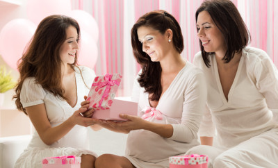 Pregnant woman opening gift on baby shower party