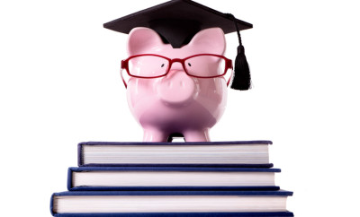 Pink piggy bank dressed as a college graduate or professor with mortar board and glasses standing on a small stack of books.  Low angle view.  Isolated on white.  Alternative version shown below.  To see my complete collection of piggy banks please CLICK HERE.