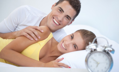 Young couple in bed in the morning smiling and looking at camera. See more LIFESTYLE images with this YOUNG COUPLE. Click on image below for lightbox.