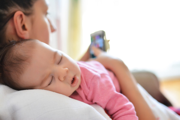 Mother In Bed With Baby Daughter Checking Mobile Phone