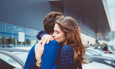 Loving young couple say good bye at airport, man and woman embracing at car parking lot.