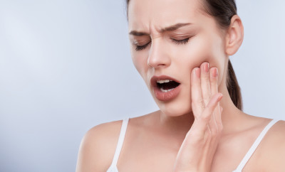 Toothache, white teeth. Head and shoulders of young woman suffering from toothache, teethcare. Painful expression on face of woman, hands near face, closed eyes